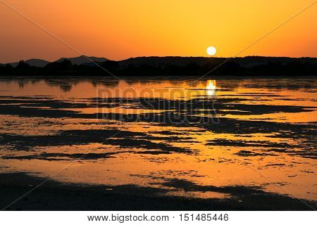 Sunset on the pond of pink flamingos in Chia Sardinia Italy.