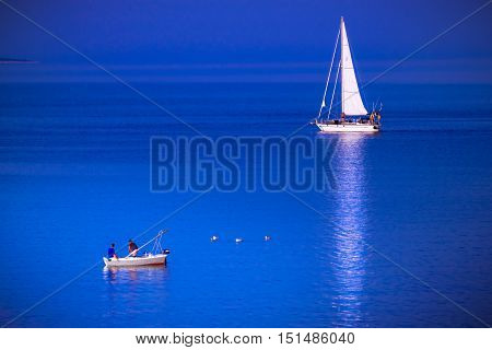 RAB CROATIA - CIRCA AUGUST 2015: Small fishing boat and sailing boat meet in the blue sea.