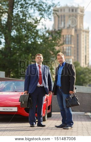 two mature business people with briefcases outside standing next to luxury supercar