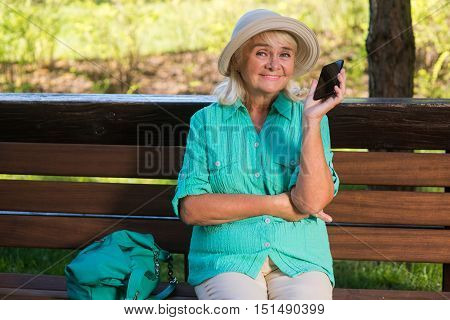 Senior woman with a phone. Lady on bench in smiling. Always in touch. New tariff of communication.