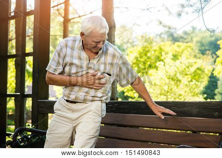 Senior man has heartache. Elderly guy near park bench. Pain is growing stronger. Pensioner needs medical attention.