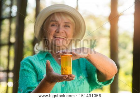 Smiling woman holds pill bottle. Tablet container of orange color. Minimum side effects. Vitamins strengthen health.