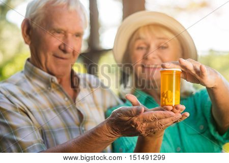 Elderly couple with pills. Smiling senior woman and man. Medicines of new era. Best drug against heart pain.