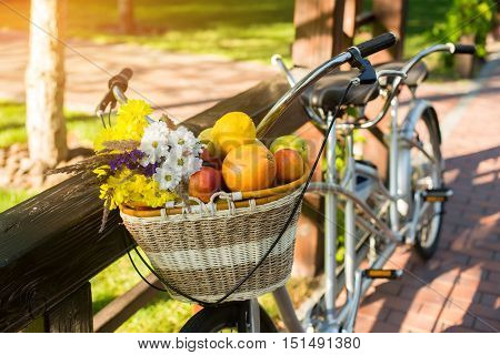 Basket with fruits and flowers. Bike near wooden fence. The energy of nature. Rest that saves health.