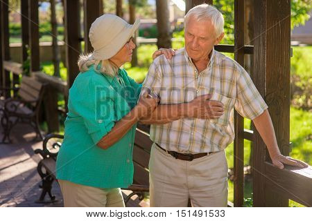Old man has heart ache. Elderly couple in the park. Show me where it hurts. Support of the closest person.