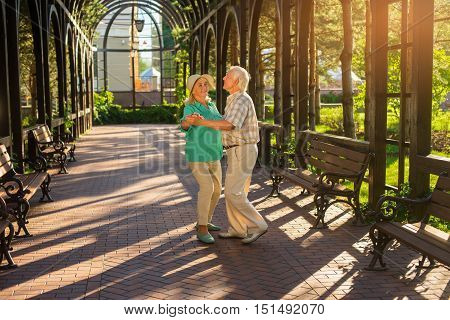 Elderly couple is dancing. Two people in the park. Like in good old times. Waltz on the alley.