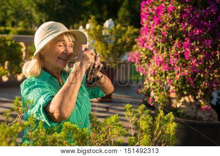 Senior woman holds camera. Elderly female in summer hat. Grandma on resort. Inspiration of photographer.