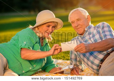 Senior couple looking at photographs. Smiling woman and man. How it all started. Glance into the past.