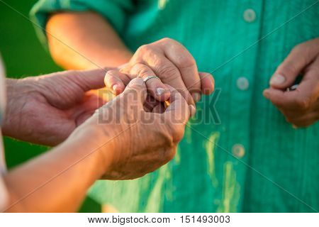 Man putting ring on lady. Hands of a senior couple. Fill your heart with love. Have no fear.