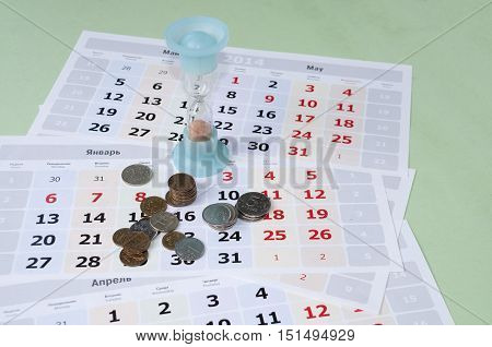 Rubles and hourglass lying on calendar sheets