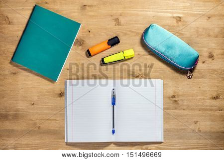 Top view workspace of the school supplies copybook, case, pen, apple, autumn maple leaf, marker on desk.