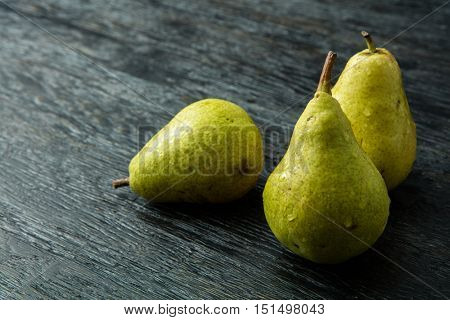 Three green pear on a black background