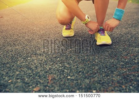 closeup of young woman runner tying shoelaces outdoor