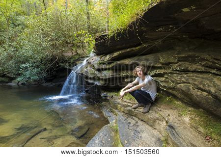 Teenage boy with long hair seated next to mountain waterfall