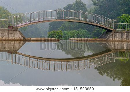 Foot bridge over a small pond with refection in the water and trees in a foggy background
