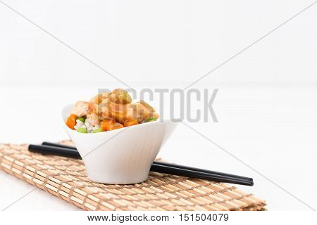 Small bowl of general tao spicy chicken served on vegetable rice.