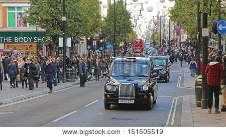 LONDON UNITED KINGDOM - NOVEMBER 23: Shoppers and Taxi at Oxford Street in London on NOVEMBER 23 2013. Oxford Street Crowded With People and Taxis in London United Kingdom.