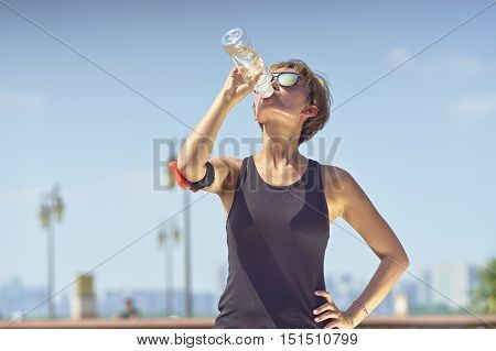 Young Asian Woman Drinking Water During Exercise