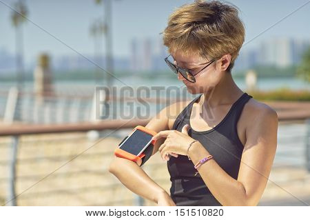 Young Asian Woman Using Smart Phone During Exercise