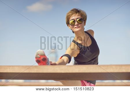 Young Woman Stretching Legs Before Jogging