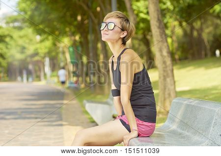 young asian woman sitting at bench after exercise