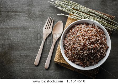 Brown Rice/Coarse rice with wooden spoon and fork rice seed . Top view.