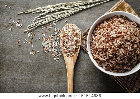 Brown Rice/Coarse rice on wooden spoon with boiled rice. Selective focus.