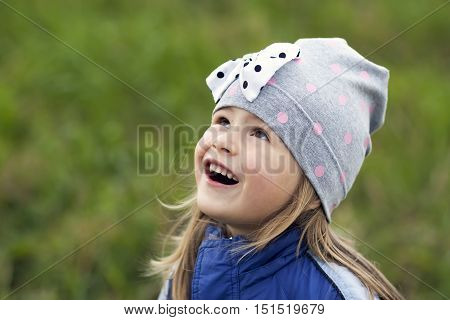 Adorable little girl posing on blurred background and smiling in to a camera. Wearing winter coat and hat. Lovely young girl in the autumn outdoors.