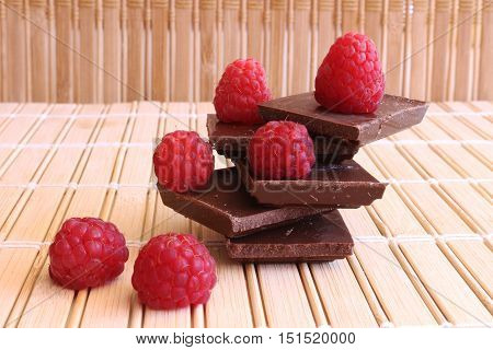 Dark chocolate pieces folded in a pile. Fresh raspberries lying on the chocolate.