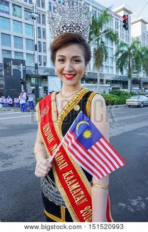 Kota Kinabalu,Sabah-Aug 31,2016:A beautiful Kadazandusun woman in traditional attire  holding the Malaysia flag during the Malaysian National day at Kota Kinabalu,Sabah,Borneo on 31st Aug 2016.