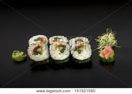 Japanese sushi rolls decorated with seaweed salad and wasabi