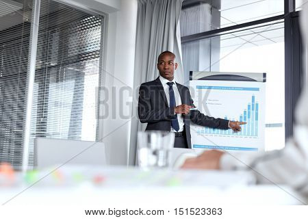 Young businessman pointing towards graph while giving presentation in office