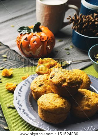Pumpkin whole grain muffins with raisins and pumpkin seeds on dark background with a halloween decorative squash. Vertical image