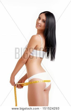 Beautiful woman measuring buttocks, wearing underwear. Slim tanned woman's body over white background. Young fitness woman buttocks measures on a white background.