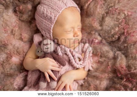 cute newborn baby on fluffy blanket in pink knitted hat and suit, with toy in hand