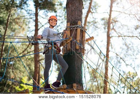 Small relaxation. Happy energetic slender woman standing on the wooden platform and smiling while having a small break