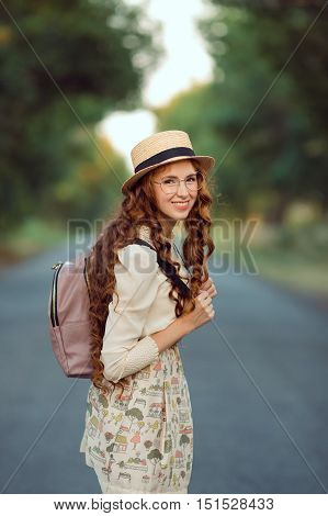 Young girl traveler enjoy the travel on foot. Portrait of happy woman walking with hat and backpack on the road and looking at camera. Adventure is coming concept