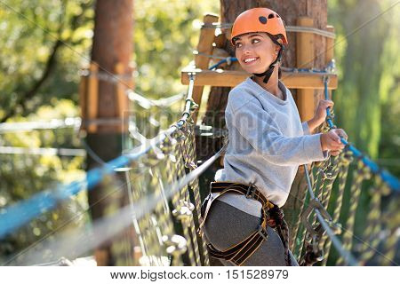 Climbing adventure. Cute joyful slender woman turning her head back and looking somewhere while being on her rope way