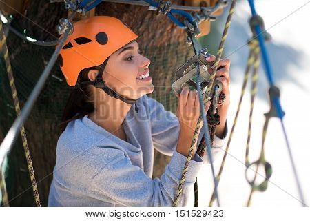 Everything is all right. Beautiful cautious sensible woman holding the mountain carabiner and looking at it while checking the safety equipment