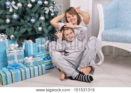 Funny Mom And Son In Pajamas Near Christmas Tree With Presents