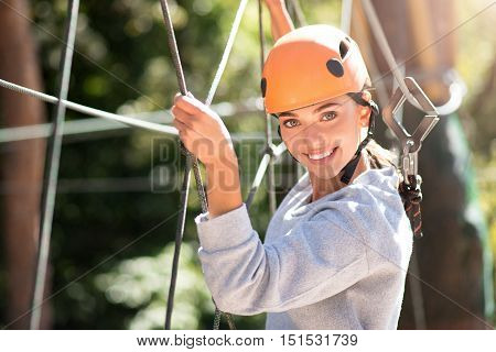 Taking precautions. Beautiful careful delighted woman wearing safety equipment and following her rope route while spending her free time in the adventure park.