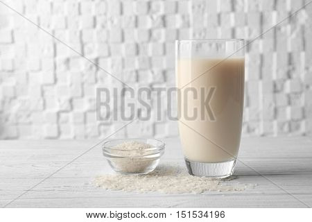 Glass of rice milk and bowl with grains on wooden table against white blurred background
