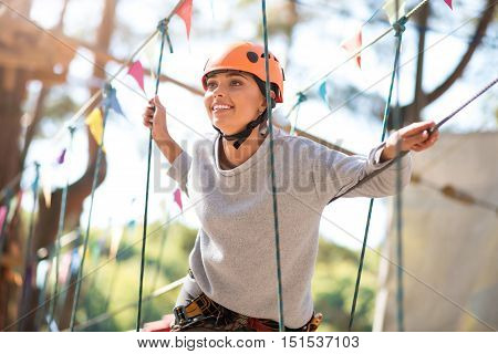 Absolute happiness. Pleasant beautiful joyful woman smiling and holding on to the ropes while enjoying her time in the rope park