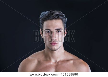Handsome, fit young man wearing only underwear standing isolated on black background, looking at camera