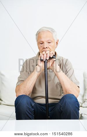 Sad old man with cane sitting pensive on a sofa