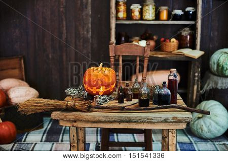 Old wooden table, orange hallowen pumpkin, dried herbs and bottles, a top view, in the studio, in the afternoon.