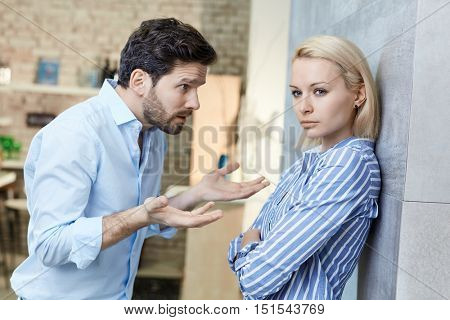 Sulky woman, explaining man at home. Relationship difficulties.