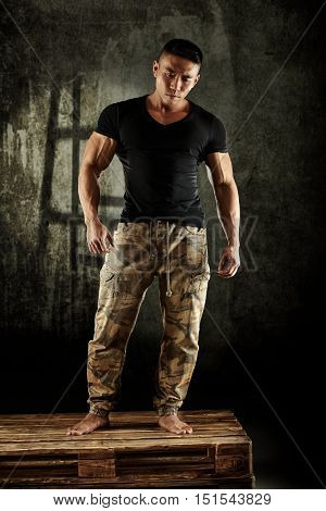 Muscular young Asian man posing in studio. Full size.
