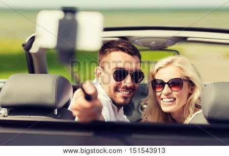 road trip, leisure, couple, technology and people concept - happy man and woman driving in cabriolet car and taking picture with smartphone on selfie stick