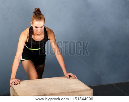 Beautiful sports woman doing push ups on fit box at gym Free spase for comercial Grey background with room for text
